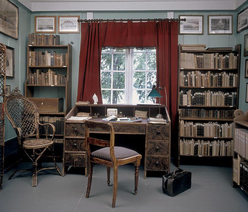 Interiør; bibliotek med bokhyller på begge sider av et vindu med røde gardiner, skrivebord og stol foran vinduet.
