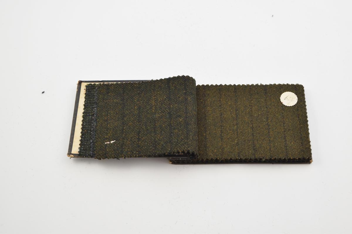 Prøvebok med 9 prøver. Tykke ullstoff uten utpreget mønster. Alle stoffer er merket med en rund papirlapp festet med melallstifter hvor nummer er påskrevet for hånd. Stoffene er i mørke grønne, brune og blå farger.  Stoff nr. 624 (grønn), 625 (blå-grønn), 626 (grønn), 627 (grønn), 628 (brun), 629 (grønn-brun), 630 (grønn-brun), 631 (blå-grønn), 632 (blå-grønn).