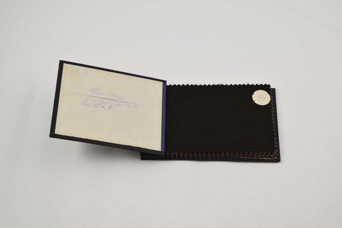 Prøvebok med 6 prøver. Middels tykke ensfargede ullstoffer. Alle stoffer er merket med en rund papirlapp festet med metallstifter hvor nummer er påskrevet for hånd.  Stoff nr. 867 (sort), 868 (grå), 940 (brun), 941 (brun), 942 (grå), 943 (grønn).