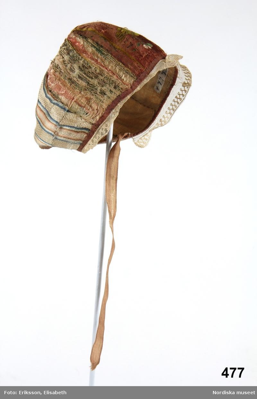 Dopmössa i pojkmodell sydd av 5 kilar i olika material, den mittersta fram av ett rosa sidenband med blommönster i grönt, vitt och gult, sidkilarna  av mycket slitna guldbrokadband och nackkilarna av siden randigt i rosa och ljusblått på vit botten. Mössan kantsydd med rosa sidenband, i framkant centimeterbred spets i trädd tyll, foder av tunn linnelärft, knytband av blekrosa sidenband. Anm. det ena knytbandet saknas. Jfr dopmössa i flickmodell  till samma dopdräkt inv.nr 478. De kommer enligt uppgift från Högsjögodset.  Berit Eldvik april 2006