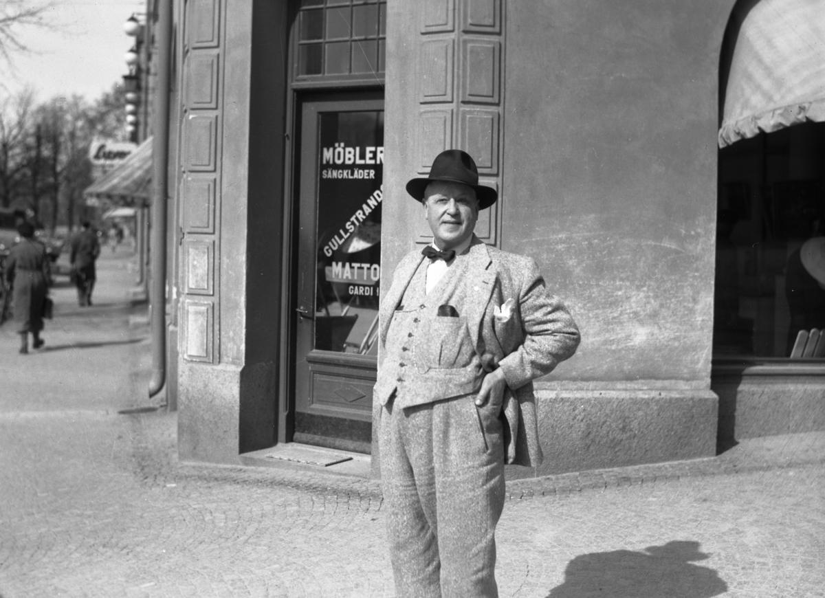Bror Monsén, ägare till Gullstrands möbler, utanför butiken i hörnet av Östra Torggatan–Kungsgatan våren 1946.