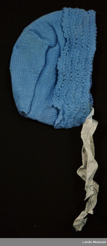 """Strikket babylue med """"havskum""""-mønster på  oppbrettet kant langs åpningen. Påsydd lysblått silkebånd for knyting. Foret med lyseblå silke."""