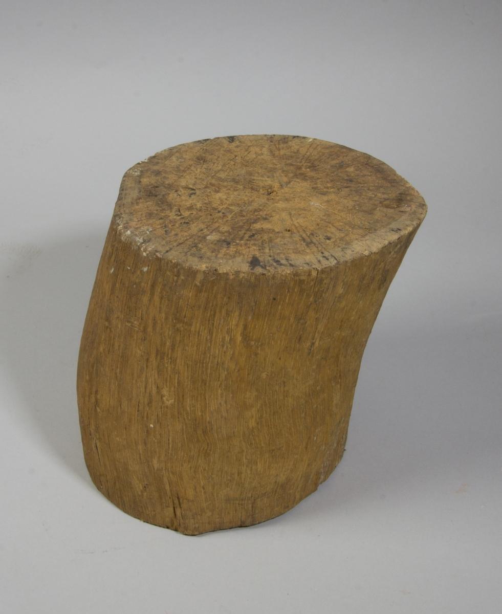 Huggkubbe av trä, cylindrisk. Spår av häftstift.