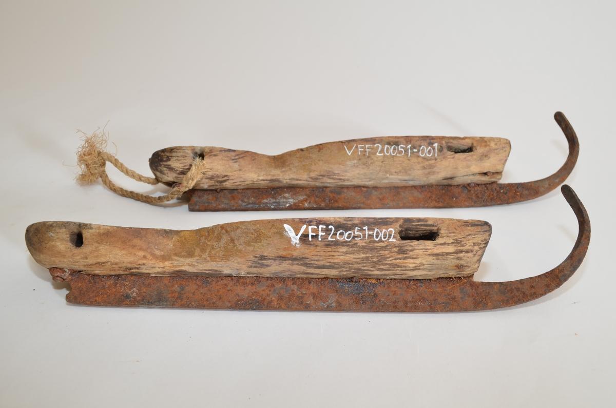 Et par skøyter til å feste på sko. Skøytene er antagelig hjemmesmidde. Skøytebladene krommer seg foran, rustet. Såla er av tre. Navn skåret inn på sålas overside på begge skøytene (utydelig).Hull til snorbinding foran og bak på såla. En av bindingene bevart.