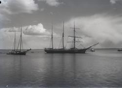 Två segelfartyg ligger för ankar vid vågbrytaren strax intil