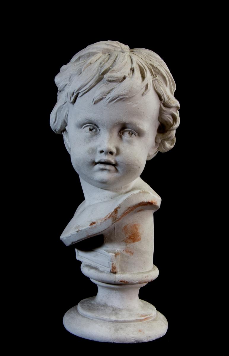 Studiemodell av gips föreställande ett barnhuvud, med huvudet lätt vridet. På rund sockel med ej ifylld inskriptionsplatta.