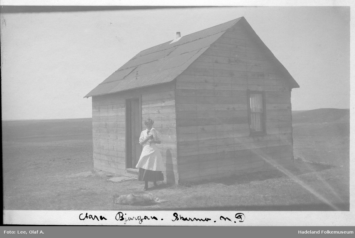 Ei dame står utenfor et hus på prærien i Nord-Dakota.