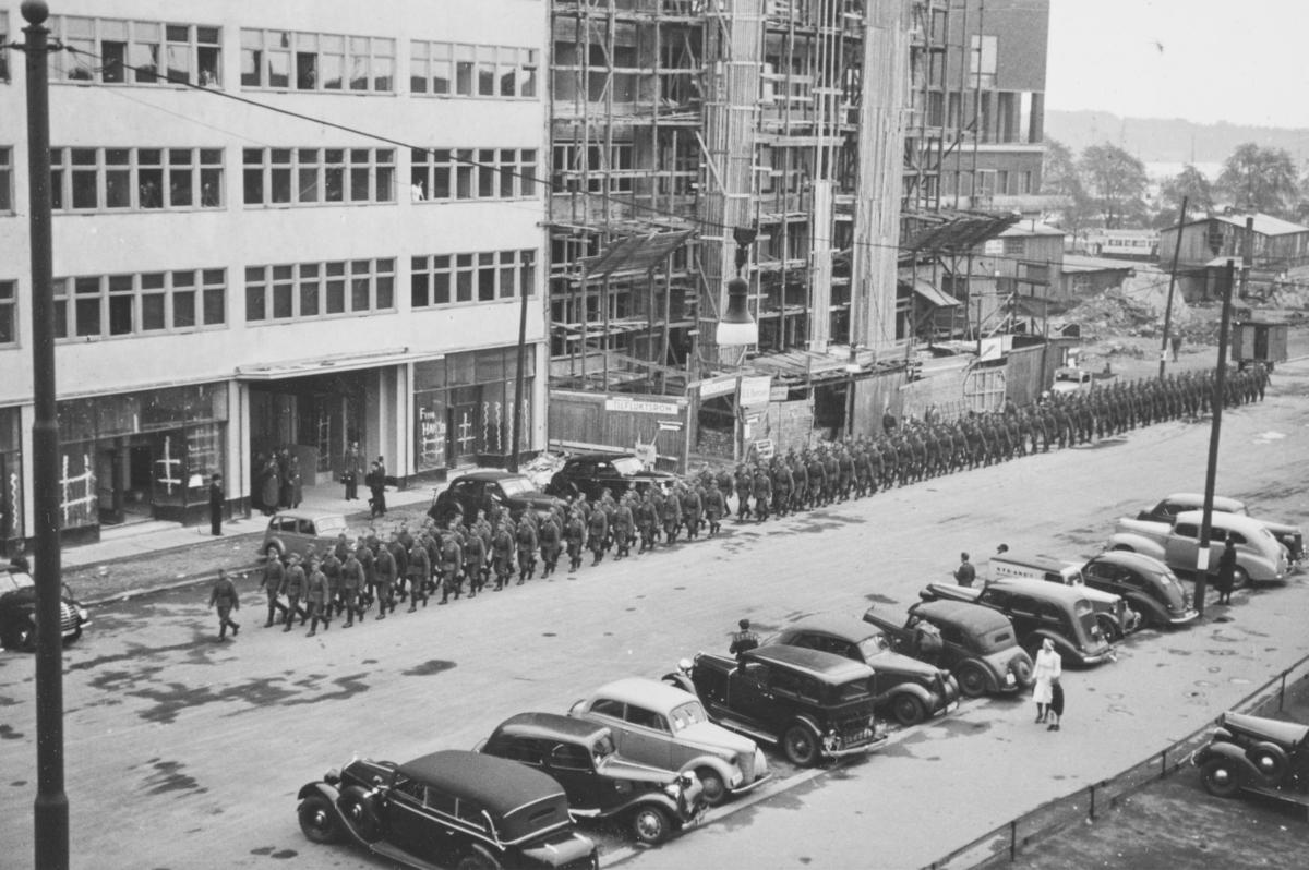 Tyske tropper marsjerer i Roald Amundsens gate. I bakgrunnen Solplassen og Oslo Rådhus under bygging.