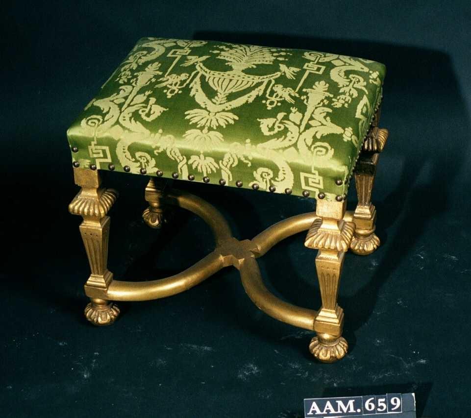 Taburett. Bøk, forgylt.  Balusterformede ben, delvis kannelerte, kvadratiske.  X-formet kryss.   Stoppet sete uten trekk, med strie.   Treverket er gipset og forgylt, rødmaling under gullet.   Fransk klassisk barokk.