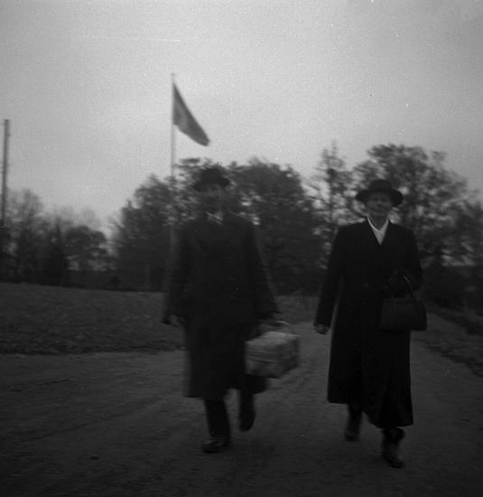 Foto av en man och en kvinna med hatt och kappa. Han håller i en spånkorg.