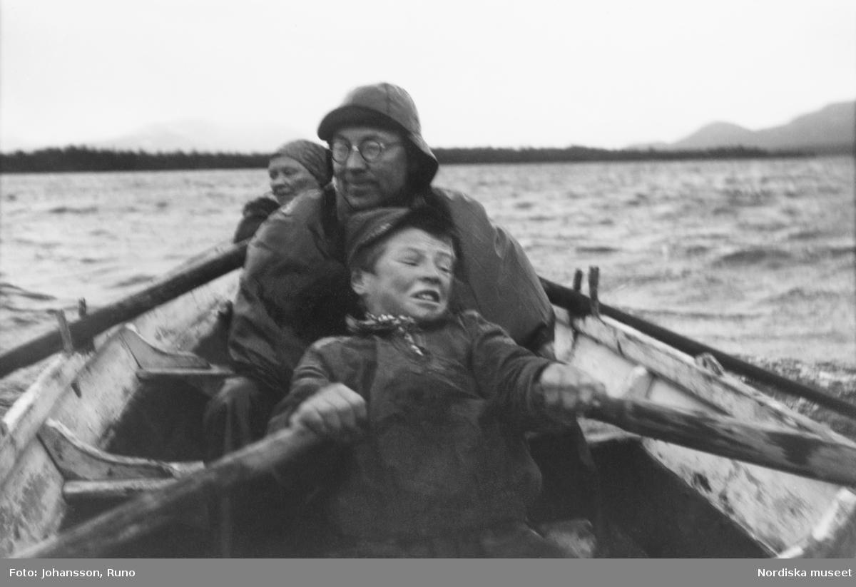 Margareta Svonni och hennes son Anders ror ut till dödsholmen i Vuoskojaure i regn och storm. mellan dem i båten sitter Ernst Manker.