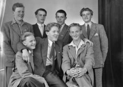 Foto av sju unga män i kostym och blazers.Ateljéfoto.