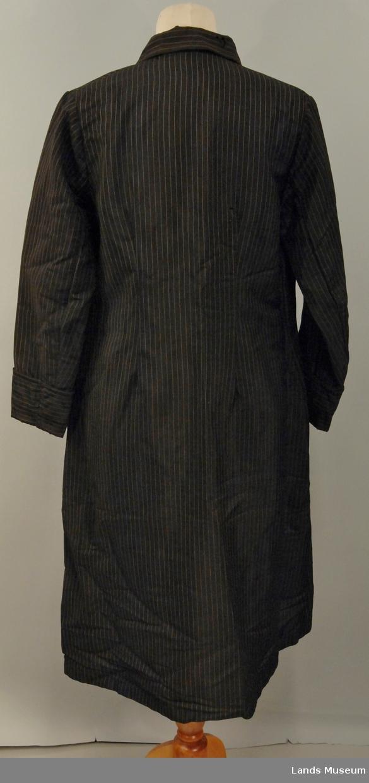 Tøyet er to-skaftsvevd med en smal gulkvit stripe i en bindingseffekt pr. 1 cm. For av satengsvevd svart bomull. Halvforing. Enkeltspent med 2 knapper. Skinkearm med oppbrett. Slag foran på kragen, svinget.