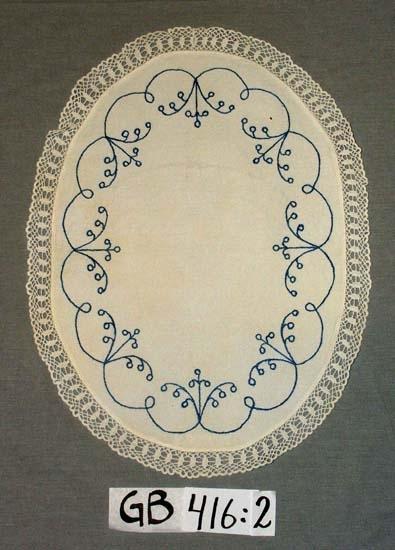 Brickduk. Broderad, med spets. Mått: Oval 450 x 340 mm + spets 30 mm. Broderi: Stjälkstygn, sytt i blått. Maskinfållad.  Handvirkad spets 2,8 cm bred, påsydd för hand.     Inskrivet i huvudkatalogen 1996-1997. Funktion: Brickduk