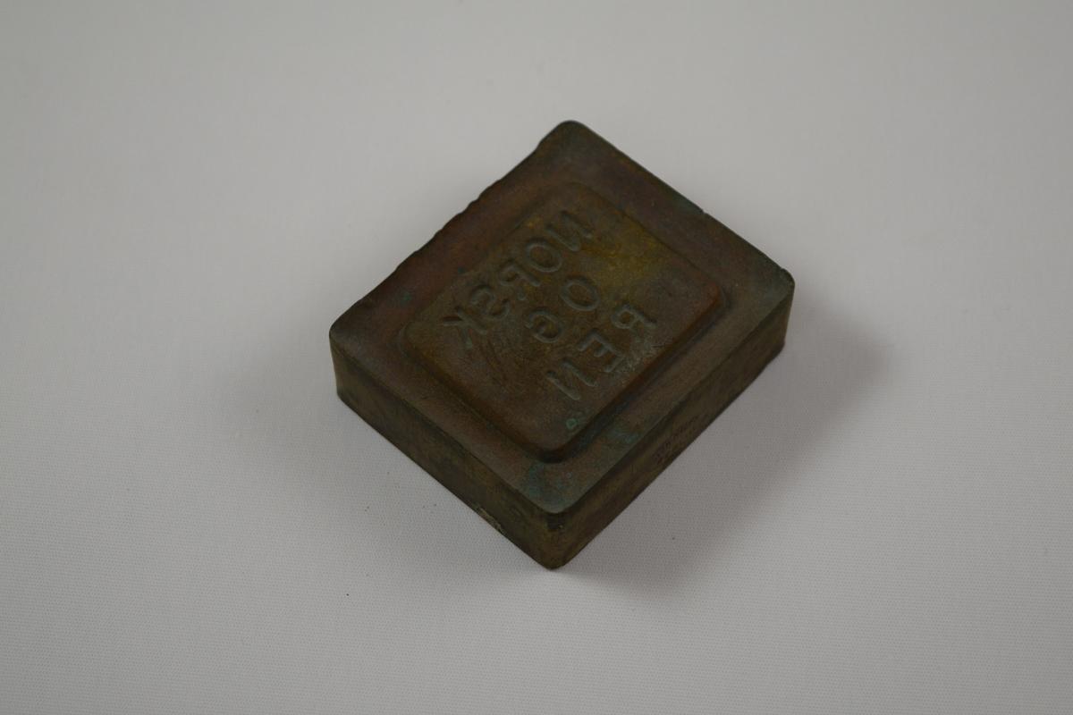 Rektangulær såpeform for produksjon av såper ved Saanums Sepefabrikk i Mandal. Kun bunn, mangler antageligvis topp. Rett stempelflate med avrundede hjørner og avrundet fordypning på ca. 0,5 cm. Opphøyet felt med nedfelt tekst sentrert på stempelflaten.