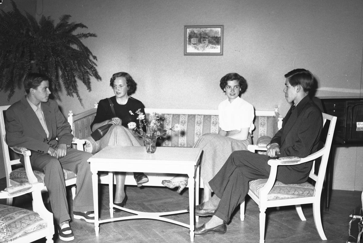 Yrkesskolornas avslutning på Stadshuset. Den 20 maj 1950. Damfrisörskeeleverna Margareta Nilsson och Ingrid Vadstedt provsitter den soffa som kamraterna på möbelsnickeriet utfört. Till vänster sitter Hans Englöf och till höger Åke Sjöstedt.