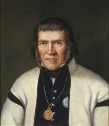 Portrett av Tallev O. Huvestad. Hvit trøye (jakke) og mørk vest kantet med rødt. Medalje hengende i kjede rundt halsen. (Foto/Photo)