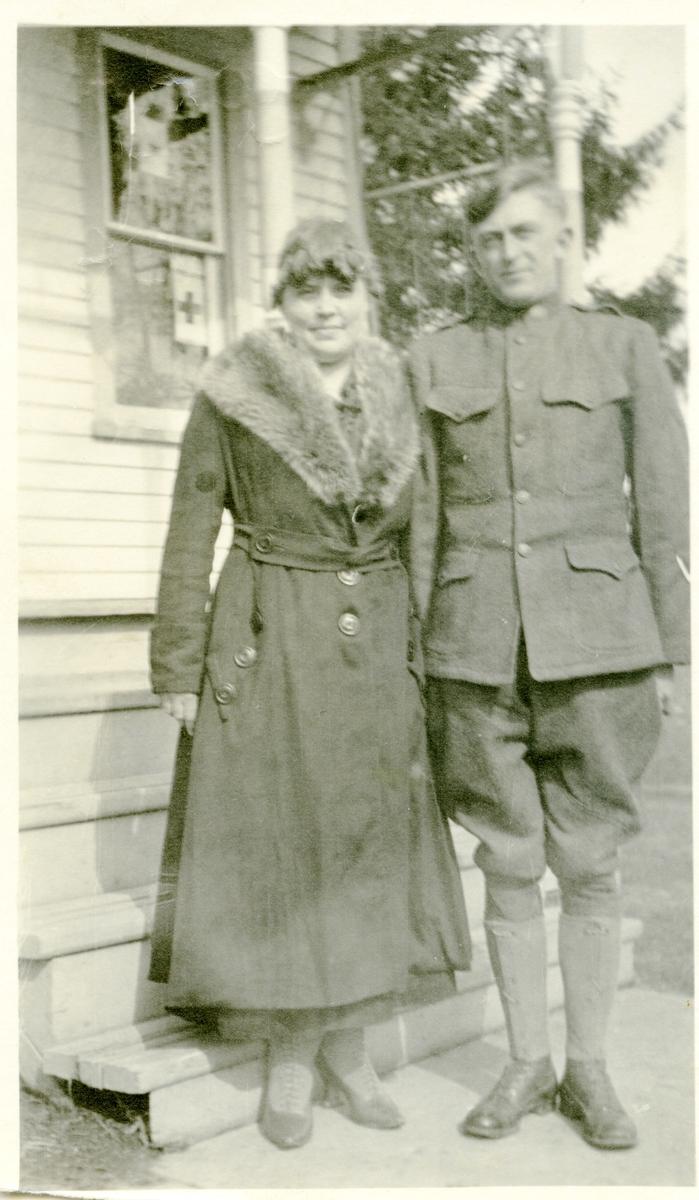 Mann og kvinne avbildet utenfor et hus. Han er kleded i en uniform og hun har en lang mørk kåpe med skinnbestetning.