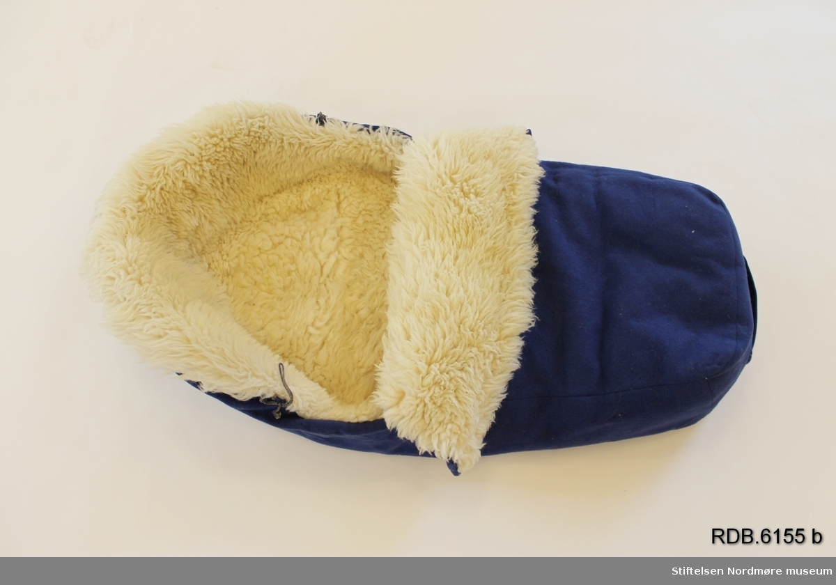 En babypose i blått ullstoff med kvitt saueskinnsfôr. Klaff foran som kan brettes ned og lukkes med 4 kvite knapper og hemper. Påsydd hempe på fotenden. Posen se hjemmesydd ut.