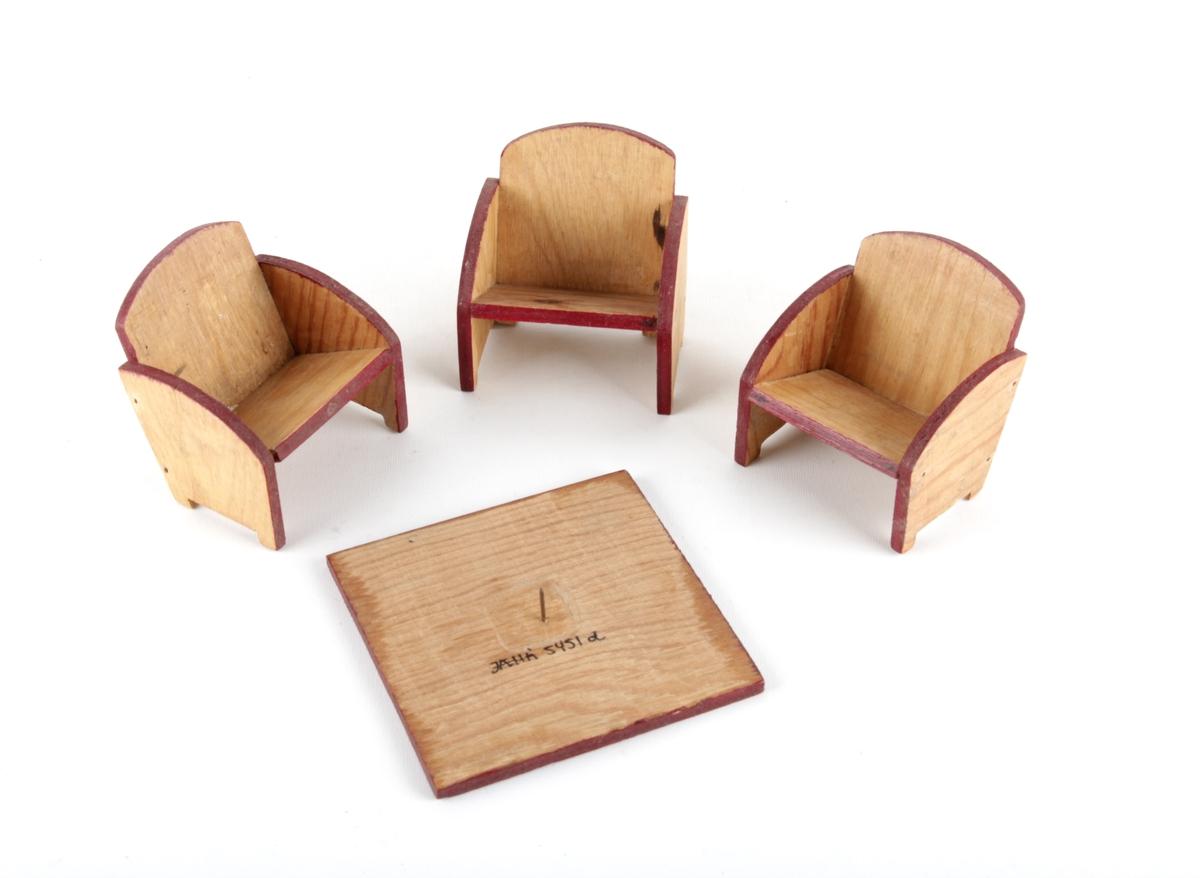 Dukkemøbler bestående av tre stoler og et bord.
