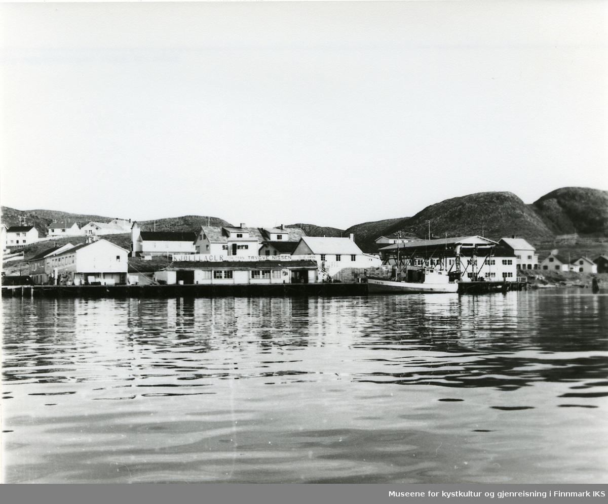 Trygve Nissens fiskebruk i Mehamn ca. 1960. Kapellet i bakgrunnen.