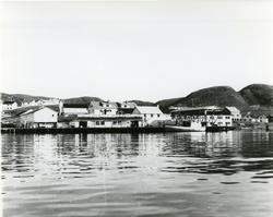 Trygve Nissens fiskebruk i Mehamn ca. 1960. Kapellet i bakgr