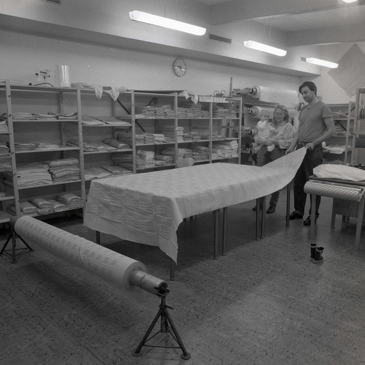 På ett bord ligger en textil utrullad och en man håller upp ena änden för att inspektera närmare. Bredvid mannen står en kvinna med ett barn i famnen och tittar på tyget. Längs väggarna står hyllor med travar av vävda textiler som varvas med inslag av tygrullar. Händelsen utspelar sig på väveriet i Näsviken 1989.