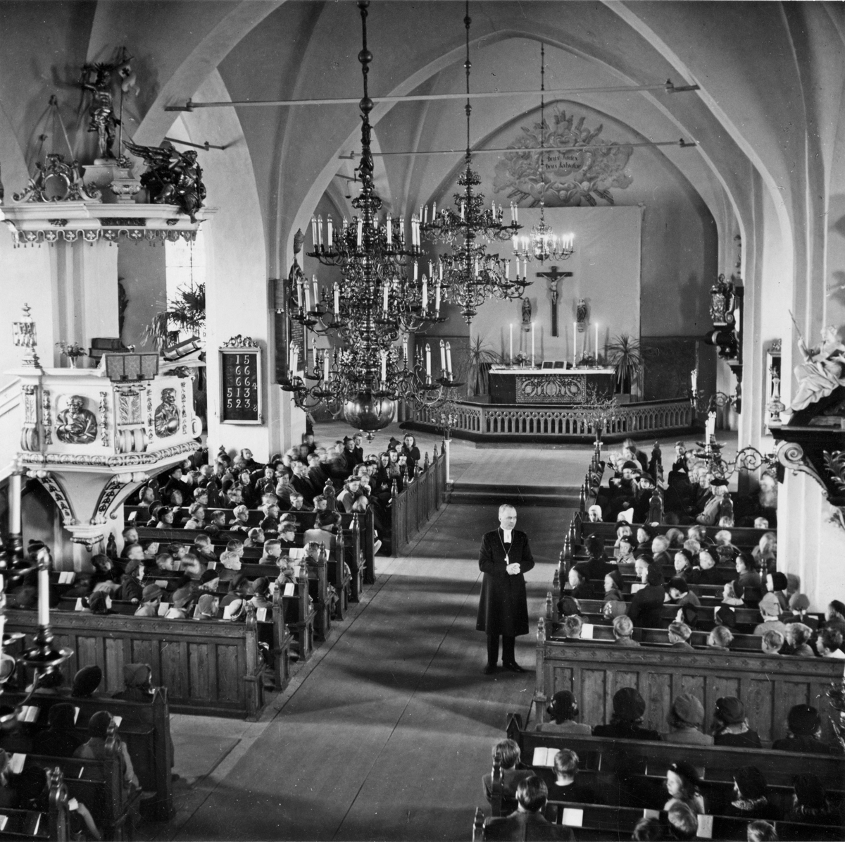 Kyrkoherde Gustavsson med församling inne i Köpings Kyrka.