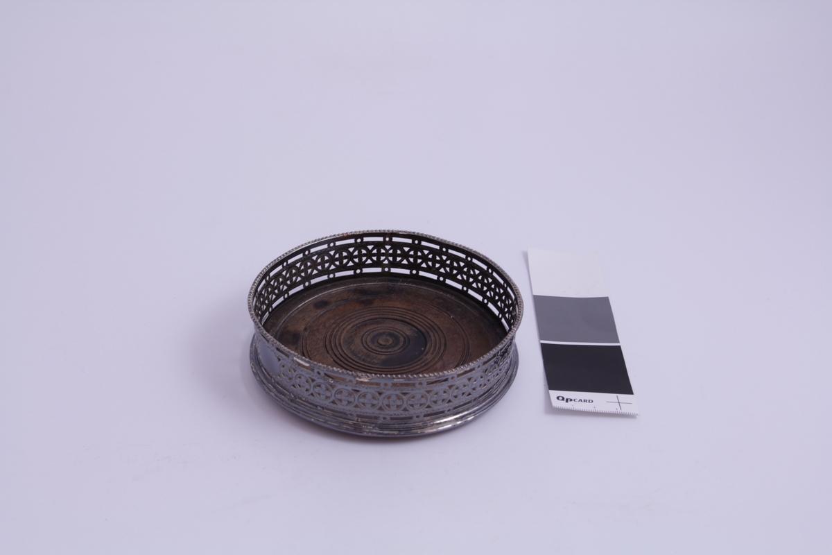 Dekor: Gjennombrutt mønster rundt hele. I midten en bred bord bestående av sirkler rundt en blomst som danner et kors.