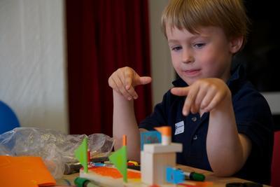 Gutt i aksjon i Barnas båtverksted. På bordet foran gutten flere lekebåter av tre.