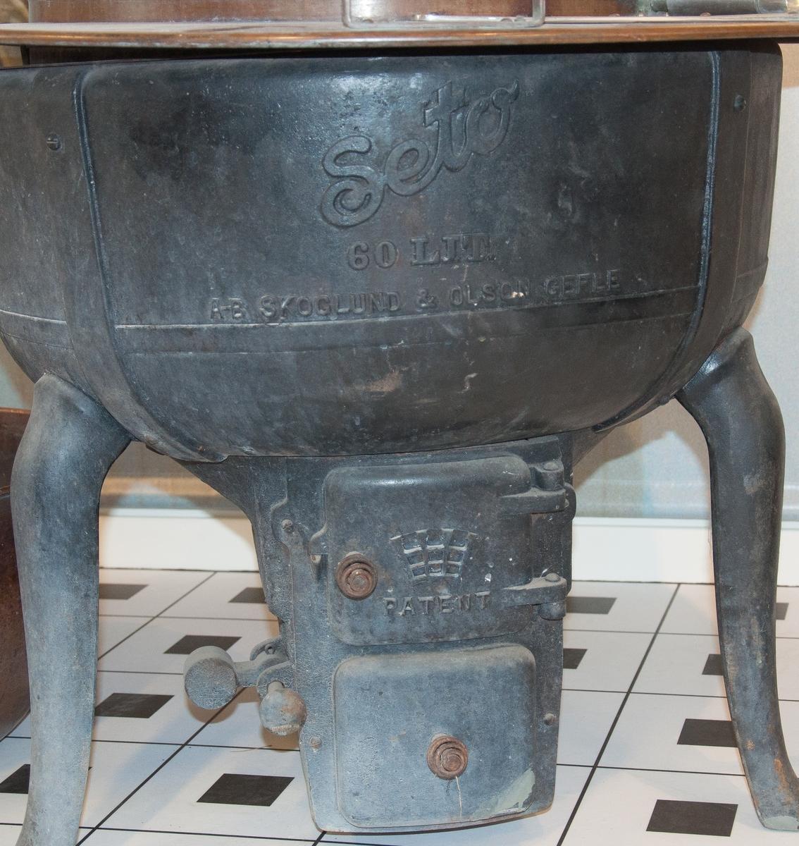 Tvättapparat av gjutjärn med kula av koppar och kupat lock av järn.  Underdelen med eldstad står på tre ben.   Kopparkulan, som är dimensionerad för att nedsänkas i grytan, är perforerad med hål, delbar med gångjärn och roteras med vev.