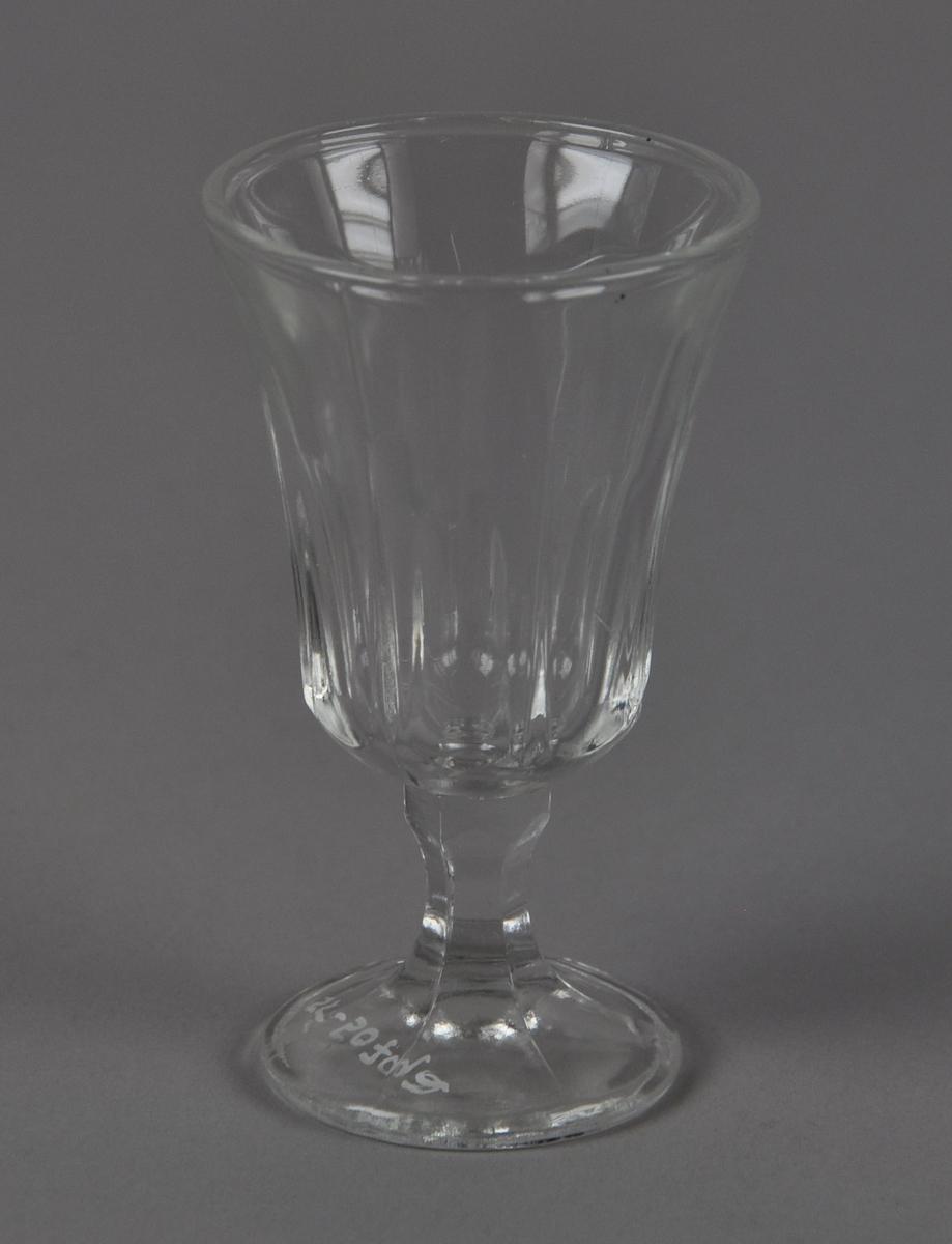 Drammeglass med fasetterte mønster på glass og stett. Glasset har utstående munnerand.