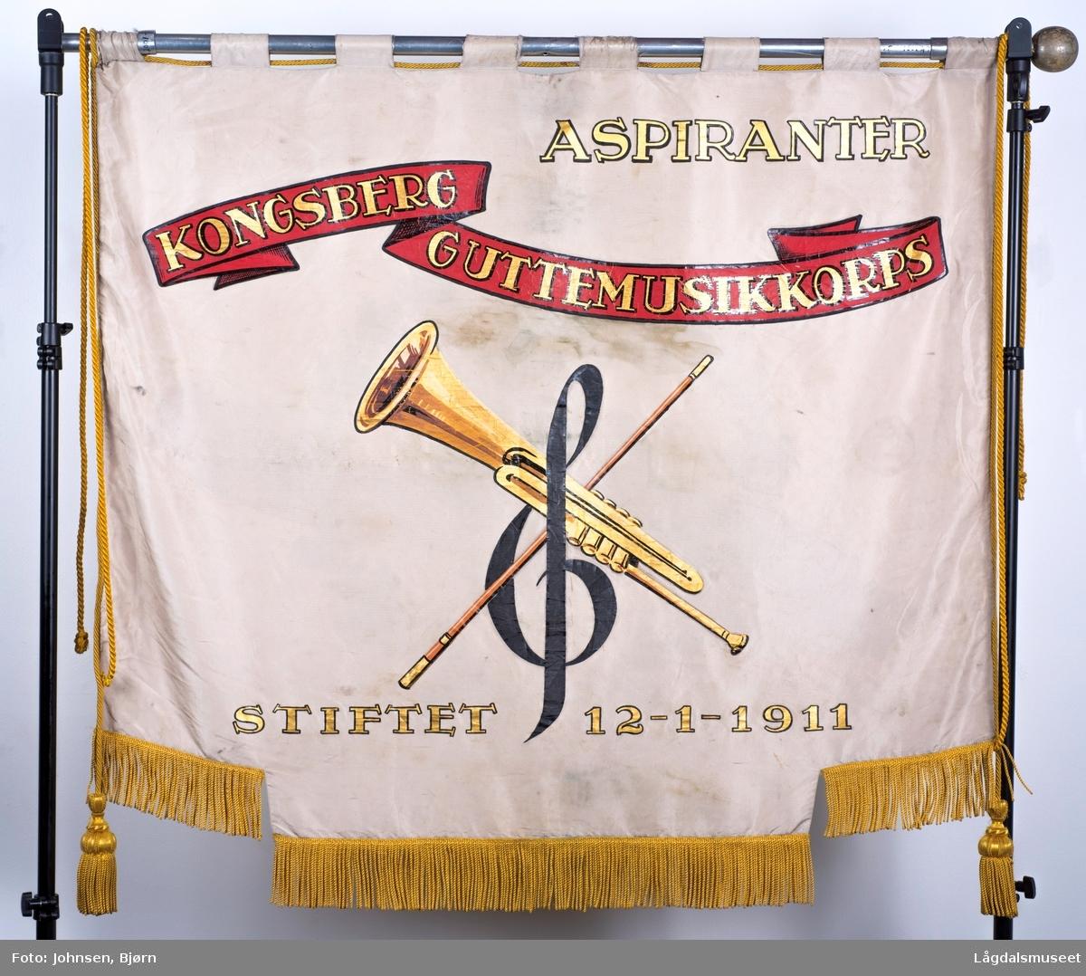 """På framsiden er det en trompet, en g-nøkkel og en dirigentpinne. Innskriften på framsiden sier: """"Aspiranter, Kongsberg Guttemusikkorps, Stiftet 12-1-1911"""" På baksiden er det avbildet Kongsbergs våpenskjold med en krans av eikeblader med nøtter. Eikebladene er et norrønt symbol på selve livet. Det er også et banner med noter som går på tvers av fanens bakside."""