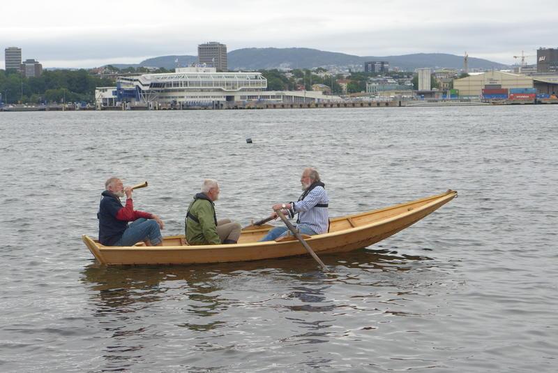 Tre menn ombord Holmsbuprammen, Oslo i bakgrunnen.