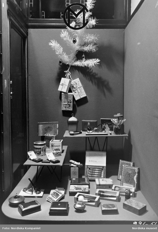 Skyltfönster på Nordiska Kompaniet, inför julen 1956. Pipor, cigarrer, askkoppar.