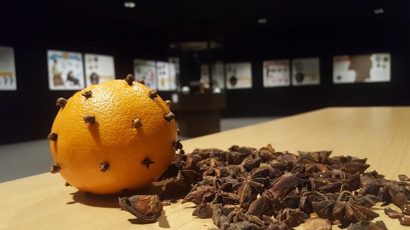 I forgrunnen appelsin med nellikspiker, ved sida av stjerneanis, i bakgrunnen utstillingsplakater.