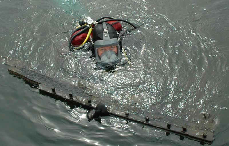 Dykker med båtdel i overflaten.