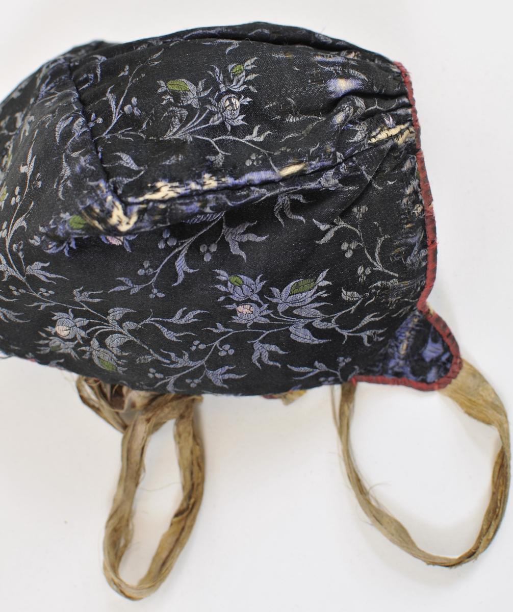 Blå lue i mønstervove silke, kanta rundt med raudt. Fora med ubleika bomull. Rynka ved pullen bak. Nedsvinga ved øyra. Samanhengande band.