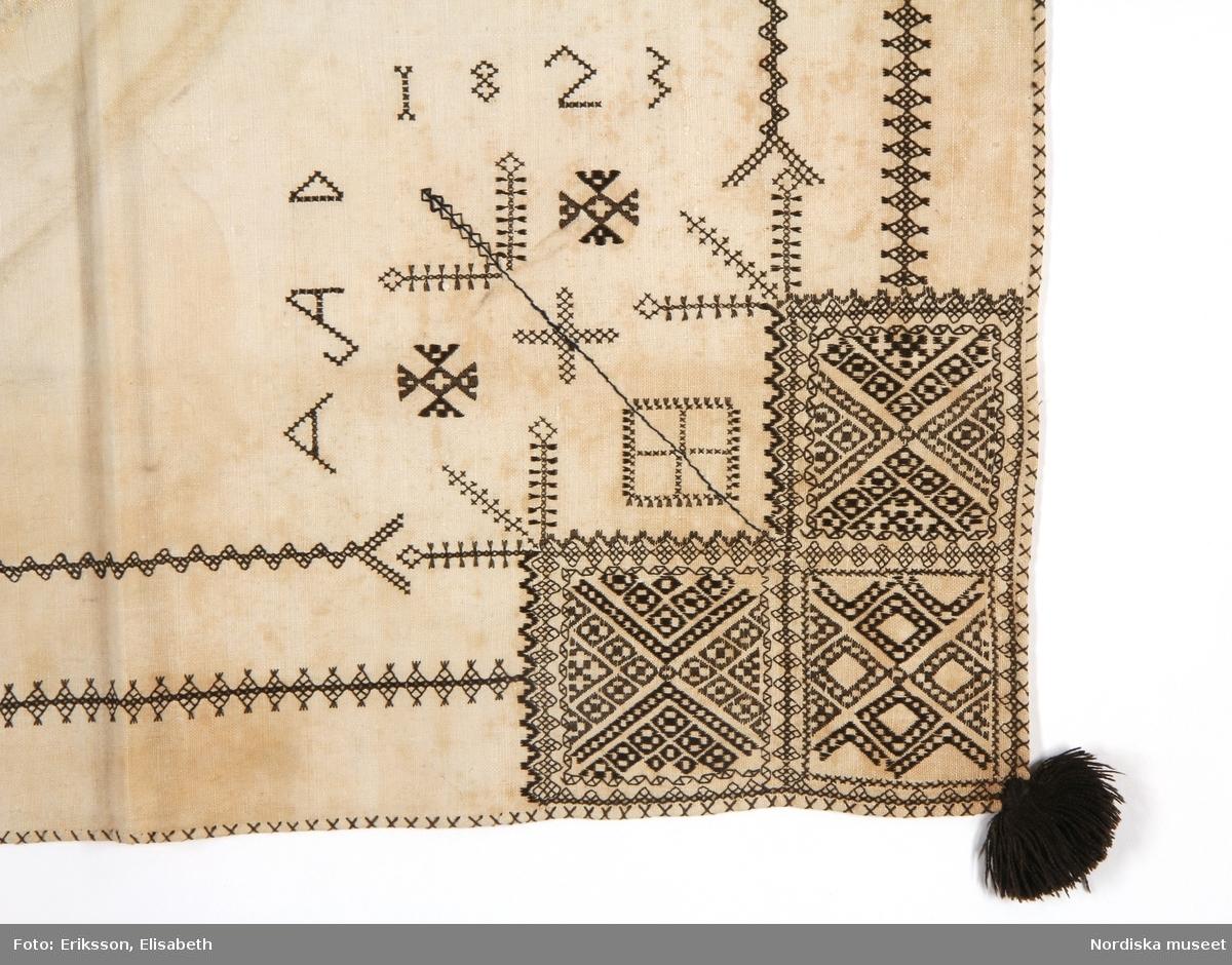 """Huvudliggaren: a, b: """" 2 'tuppasklän' fr. Leksands sn; NedanSiljans fgd; Dalarna. (Tupphalskläder) a. Märkt: 'AAD 1823' b: Märkt: 'AKD 1839' Ink. af handlaren K.Davidsson i Stockholm jämte 59,280-59,282 - [...] 2/5 1889 Bil.281.1889""""  Bilaga: Finns ej.  Katalogkort: Finns ej.  a: Halskläde av tuskaftat halvlinne. Kvadratisk form, avsett att vikas i tresnibb, broderad i tre hörn i  svartstick. Broderierna är utförda i svart silke. Mönstren är geometriska men oregelbundna,  Rombiska former i förstygn med tofssöm mellan huvud- och hörnmotiv. Sömsätten i broderierna är  rätlinjig plattsöm, förstygn, efterstygn, korssöm och tofssöm . Svarta silkestofsar i alla hörn. Broderad märkning i korssöm: """"AAD 1823"""" vid huvudmotivet. I det ovikta hörnet är huvudmotivet placerat, detta upprepas sedan halverat på båda snibbarna. Fållen översydd med kastsöm i kryss i svart silke runtom. Den del som inte var synlig utåt är odekorerad. Anm: Gulnat. Fläckigt. Bristning i mittvikning ihopsydd på baksidan.  b: Halskläde av tuskaftat halvlinne. Kvadratisk form, avsett att vikas i tresnibb, broderad i tre hörn i  svartstick. Broderierna är utförda i svart silke. Mönstren är geometriska men oregelbundna,  Rombiska former i förstygn  med tofssöm mellan huvud- och hörnmotiv. Sömsätten i broderierna är  rätlinjig plattsöm, förstygn, efterstygn, korssöm och tofssöm. Svarta silkestofsar i alla hörn. Broderad märkning i korssöm: """"AKD 1839"""" vid huvudmotivet. I det ovikta hörnet är huvudmotivet placerat, detta upprepas sedan halverat på båda snibbarna. Fållen översydd med kastsöm i kryss i svart silke runtom. Den del som inte var synlig utåt är odekorerad. Anm: Gulnat i mittvikningen.  Svartstick är ett broderi som förekommer i några socknar runt södra Siljan i Dalarna. Det broderas som dekor på vita halskläden till folkdräkten. Halsklädet bars till högtidsdräkten - kyrkdräkten, och användes i högmässan vid de stora helgerna och bröllop.  Utdrag ur Odstedt Ella, (1953), Övre Dalarnas bondekultur unde"""