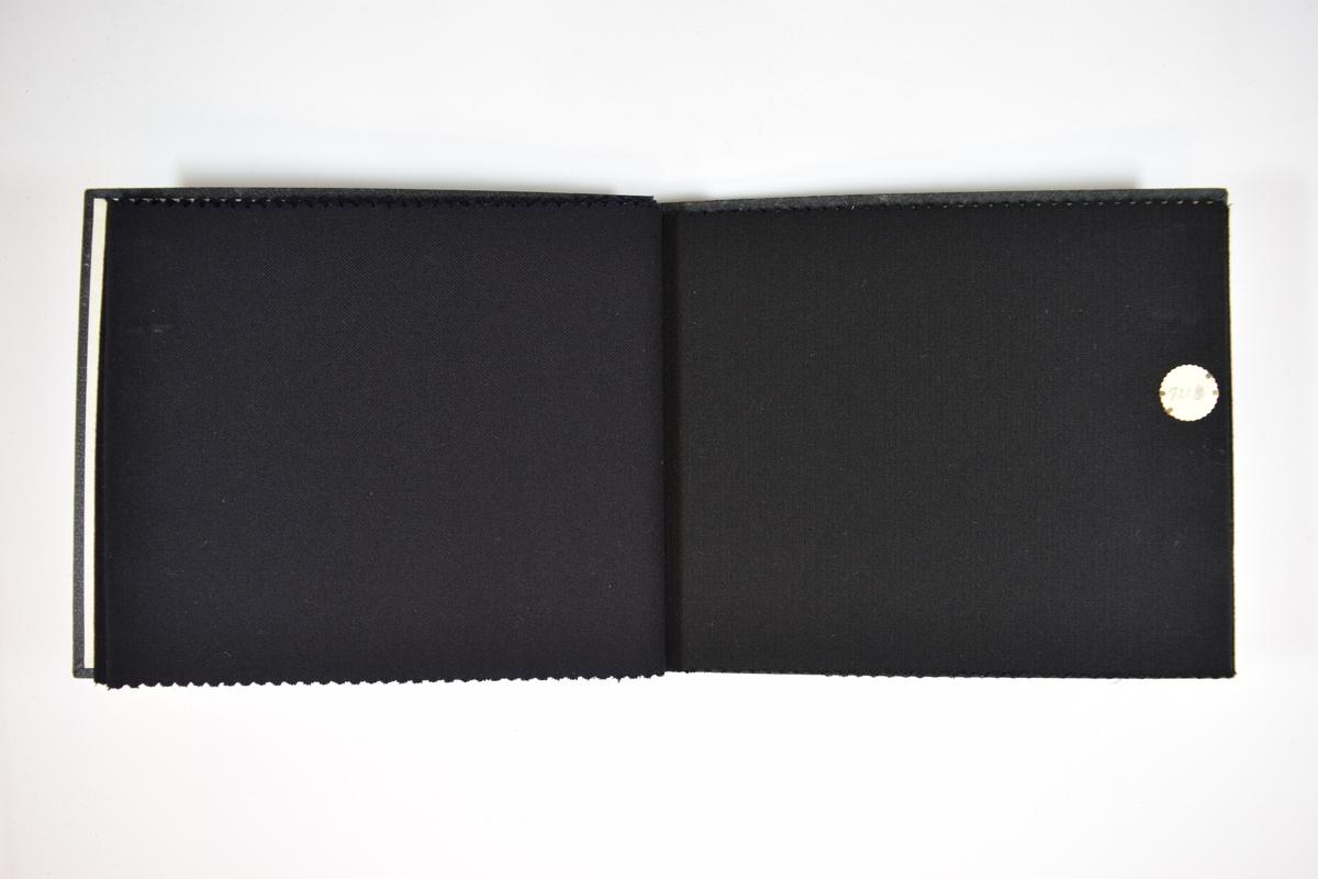 Prøvebok med 5 stoffprøver. Relativt tynne ensfargede mørkeblå eller sorte stoff med fiskebensmønster eller skrå striper i veven. Kyperbinding/diagonalvevd. Stoffene ligger brettet dobbelt slik at vranga skjules. Stoffene er merket med en rund papirlapp, festet til stoffet med metallstifter, hvor nummer er påført for hånd.    Stoff nr.: 728, 728B, 728G, 1300, 1300B