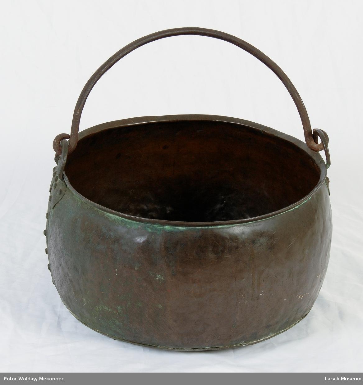 Form: buet vegg, sammenføyd og festet til bunnen med kobbernagler. ørene festet med kobbernagler. i disse henger hank av jern.