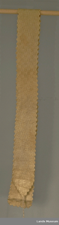 Strikket i einfarga mønsterstikk med ruter. Hekla kant rundt (musetagger) Bånd til å knyte med i bomull.