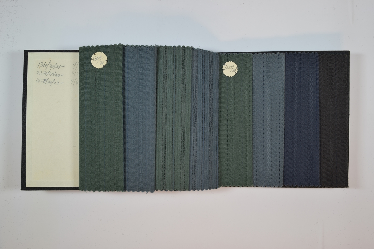Rektangulær prøvebok med 8 stoffprøver. Relativt tynne stoff med ulike striper, noen også med fiskebenmønster. Kyperbinding/diagonalvevd, samt toskaftsvev. Stoffene ligger brettet dobbelt i boken slik at vranga dekkes. Stoffene er merket med en rund papirlapp, festet til stoffet med metallstifter, hvor nummer er påført for hånd.   Stoff nr.: 1310/20, 1310/21, 2220/29, 2220/30, 1555/20, 1555/21, 1555/22, 1555/23.