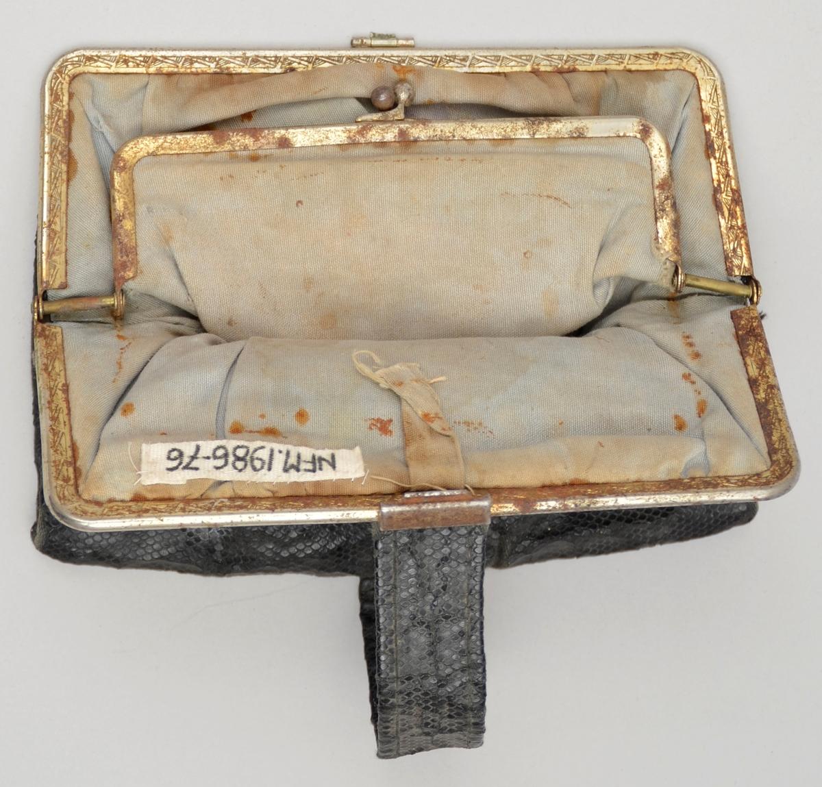 Lita handveske utan handtak. Svart skinnimitasjon. Lukking med metall-lås. Kant i metall. Lomme med knepping inni. Fôra med bomullsstoff. To kalenderlappar med dato 10 og 13 mai 1944 oppi lomma.