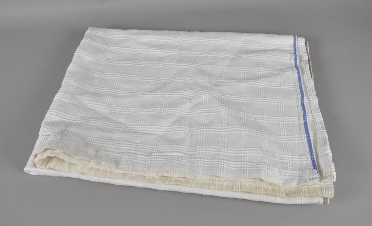 Hvit gardin med rutemønster. Stoffet er noe flekkete.