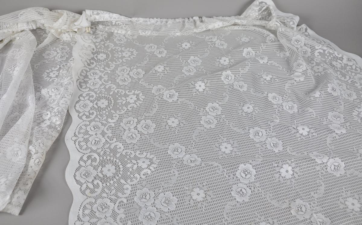 Kniplet gardin av hvit tekstil, med gjennombrutt blomstermønster. Henger i en opphengstråd.