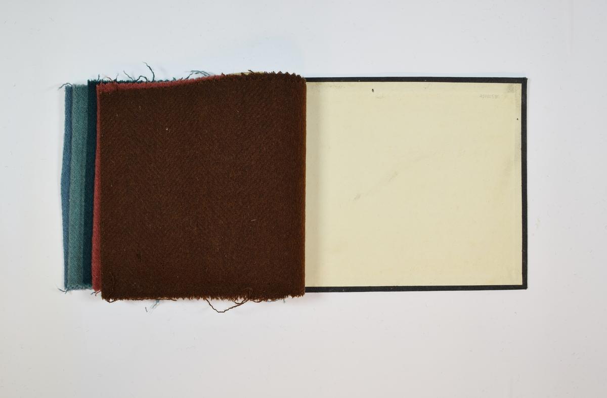 Prøvehefte med 6 prøver. Middels tykke ensfargede stoff med diskret fiskebensmønster - mønsteret er likt på forsiden og baksiden av stoffet. Stoffene ligger brettet dobbelt i heftet. Stoffene er merket med en rund papirlapp, festet til stoffet med metallstifter, hvor nummer er påført for hånd. Heftet har stiv bakplate og en papp-plate der heftet er stiftet som dekker ca. 5 cm forsiden. På pappen på forsiden er det en innskrift som indikerer at alle stoffene har kvaliteten 1940.   Stoff nr.: 1940/11, 1940/12, 1940/13, 1940/14, 1940/15, 1940/16.