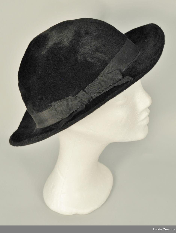 Hårfilt. Svart for med rynketråd. Enkel, rund pull. Svart hattebånd med sløyfe av svart rips.