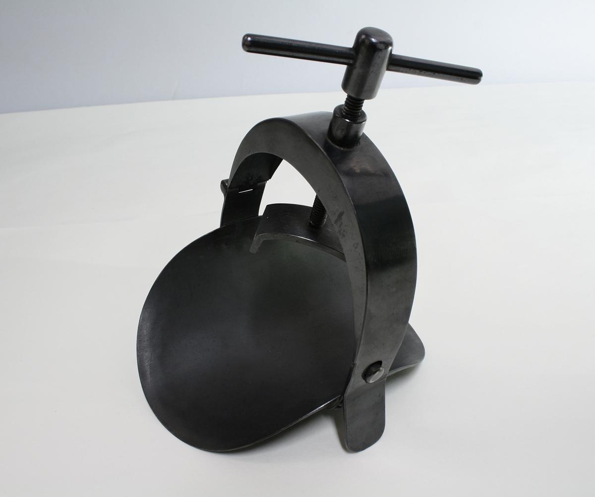 Sirkelformet tvinge i sort  metall. Sirkelen tres på et lem, f.eks arm eller legg og skuren stammes.