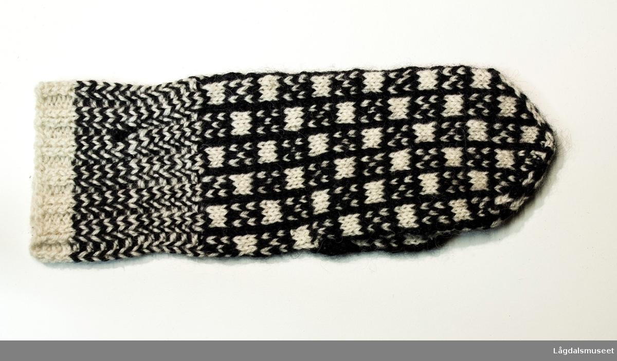 Strikket votter i svart og hvit med rutet mønster.